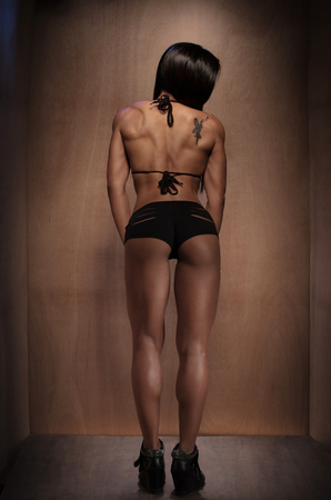 cuerpo femenino: Encuadre de cuerpo entero Foto de una atlética mujer joven, vistiendo ropa interior Negro, de pie y frente hacia atrás contra Brown Pared.