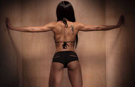 atletismo: Vista posterior de una atractiva mujer atlética con tatuaje en la espalda Sosteniendo la pared de madera en los lados usando sus dos manos.