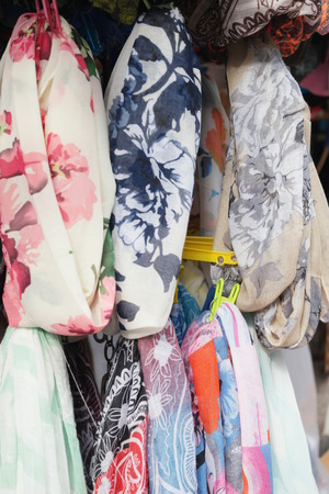 silken: Colorful display of assorted trendy scarves with floral patterns hanging on rails in a shop or street market, close up view