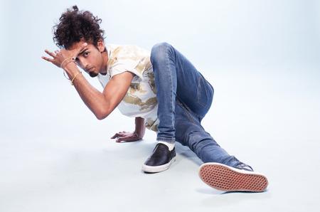 danseuse: Jeune Homme aux cheveux bouclés Danseuse dans un Hip Hop Pose sur le sol, en regardant la caméra sur fond blanc dans le studio.