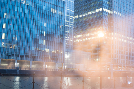 after hours: Low angle view of two glass office building exteriors from across river with ethereal mist in foreground Stock Photo