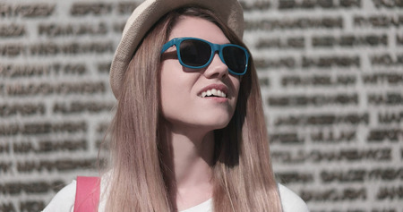 stylish woman: Close up Fashionable Pretty Young Woman, Wearing Sunglasses and Hat, Looking Up on a Sunny Day Against Concrete Building Wall Stock Photo