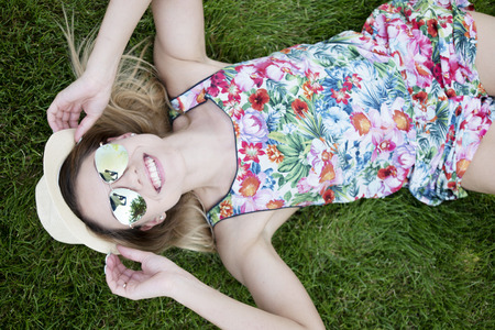 summer dress: Pretty Young Woman in a Trendy Outfit Smiling at the Camera From High Angle View While Lying on the Green Grasses and Holding her Sunglasses.