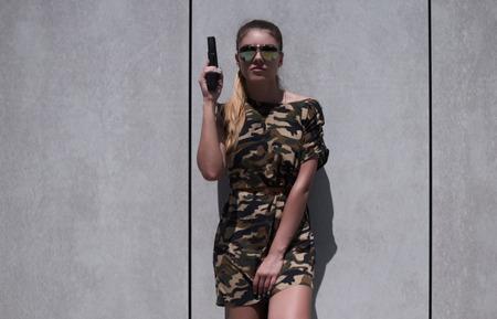 donna sexy: Donna Con indossare Pistola abito mimetica contro il muro