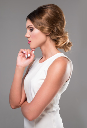 woman hairstyle: beauty woman with retro hairstyle looking to the side wearing white dress