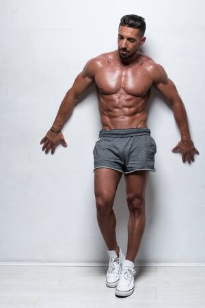 portrait: Three Quarter Length Portrait of Muscular Man Standing Shirtless with Hand on Hip Wearing Gray Athletic Shorts in Studio with White Background and Looking to the Side Stock Photo