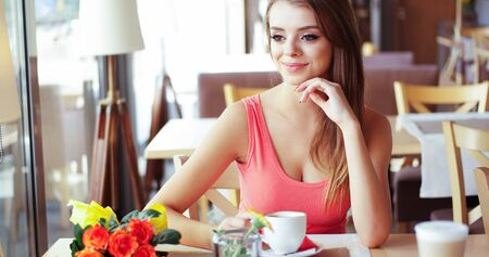 ravishing: Portrait of Smiling Young Woman with Mug of Coffee Sitting in Sunny Window Seat of Trendy Cafe Restaurant