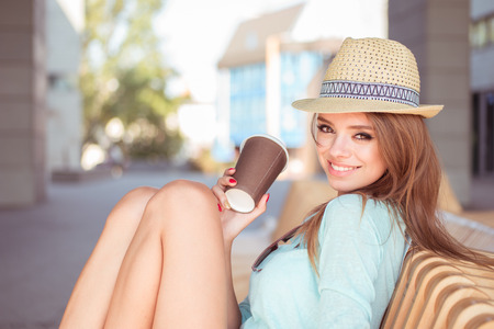 caffee: Attractive Young Woman with Cup of Coffee Sitting on the Chair and Smiling at the Camera.