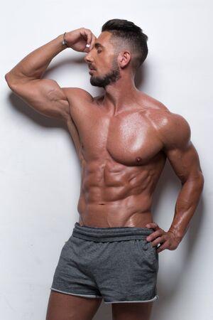 musculoso: Encuadre de tres cuartos Retrato de Muscular Man Standing descamisado con la mano en cadera llevar gris pantalones cortos deportivos en estudio con fondo blanco y mira a la cara Foto de archivo