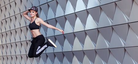 architectural wall: Young Female Hip Hop Dance Jumping in the Air Against Modern Architectural Wall Background.