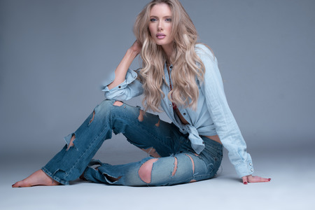 jean: Gorgeous slender young trendy blond woman in slashed designer jeans sitting barefoot relaxing on the floor looking at the camera with a serious expression
