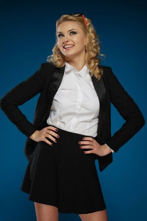 jaunty: Sexy trendy young blond woman with a vivacious smile posing with her hands on her hips in a black miniskirt, three-quarter portrait over a dark blue background