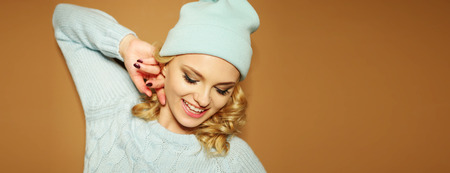 conspiratorial: pretty blonde woman wearing winter hat and sweater