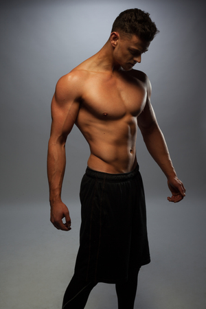 sixpack: Sexy shirtless male model young bodybuilder posing over gray background. Studio shot standing on the side