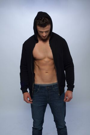 enticement: Fashion portrait of young man in black hoody