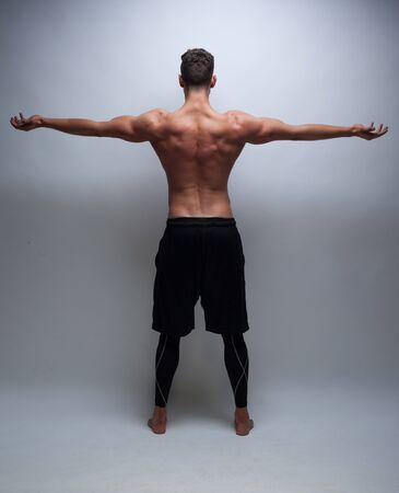 man behind: male model with muscular back on grey