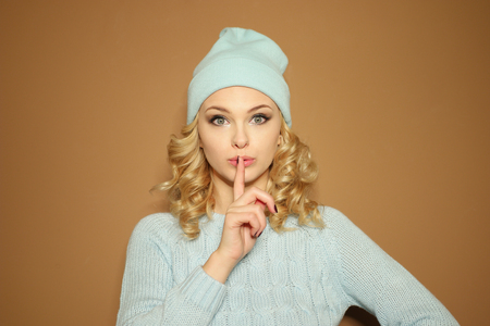 shushing: Gorgeous young woman with blond ringlets in a green knitted winter outfit making a shushing gesture with her finger to her lips as she asks for silence, over light brown