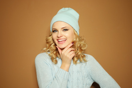 ringlets: Gorgeous young woman with blond ringlets in a green knitted winter outfit smiling,over light brown