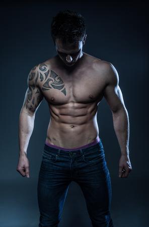 セクシーな上半身裸の男性モデル若いボディービルダーは、灰色の背景の上でポーズします。スタジオ側に立っての撮影