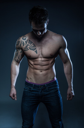 Sexy shirtless male model young bodybuilder posing over gray background. Studio shot standing on the side