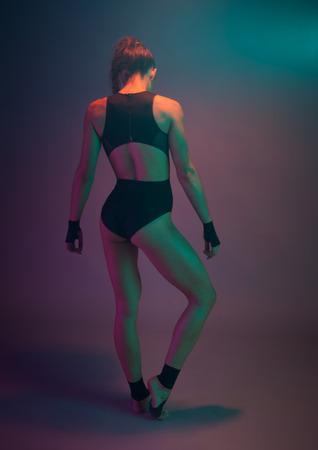 sexy female fitness acrobatic dancer posing in the studio