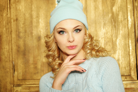 shushing: Gorgeous young woman with blond ringlets in a green knitted winter outfit ,over light brown Stock Photo