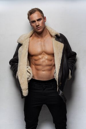 nude male body: Muscular handsome sexy guy posing wearing jacket