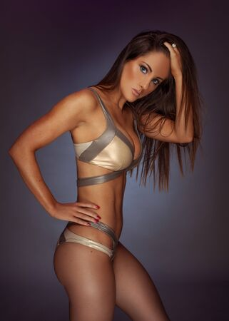 brunette girl: Sexy pose of a dark haired woman wearing gold bikini