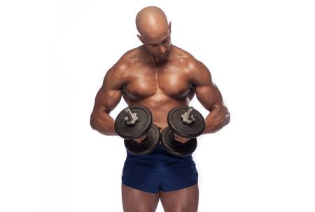 nackte brust: junger Mann mit nacktem Oberkörper heben Hanteln. Passender junger Mann mit Hanteln Ausübung auf grauem Hintergrund. Bild des verschwitzten Bodybuilder. Lizenzfreie Bilder
