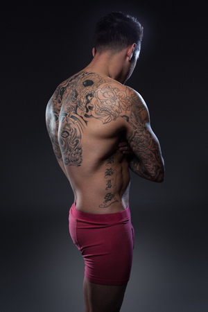 shirtless tattoed man from the back