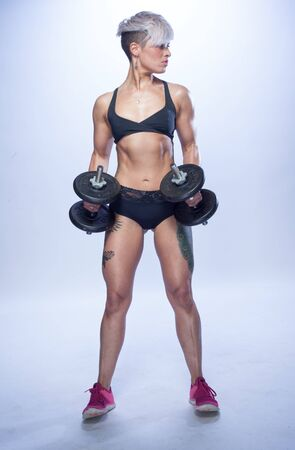 Fitness young woman standing with dumbells on grey
