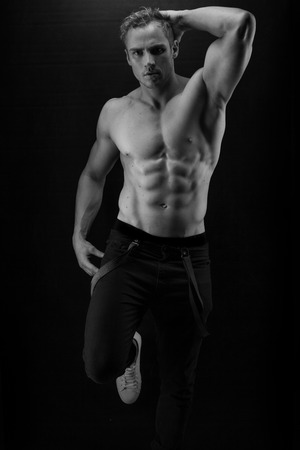 6 pack: Muscular handsome sexy guy posing on black