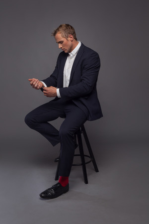 elegant young fashion man in tuxedo sitting on the chair Stock Photo
