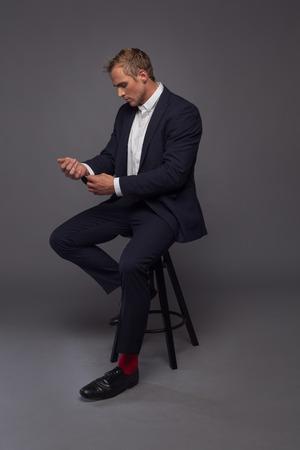modelos negras: elegante hombre de moda joven en el smoking que se sienta en la silla