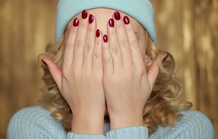 hands covering face: Young blond woman wearing a knitted blue winter outfit covering her face with her hands with manicured painted red nails Stock Photo