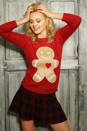 ginger bread man: Sultry blond woman in red ginger bread man sweater Stock Photo