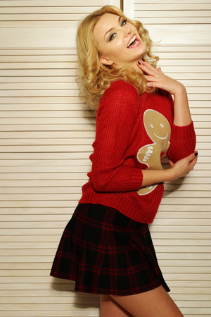 checkered skirt: Sultry blond woman in red ginger bread man sweater Stock Photo