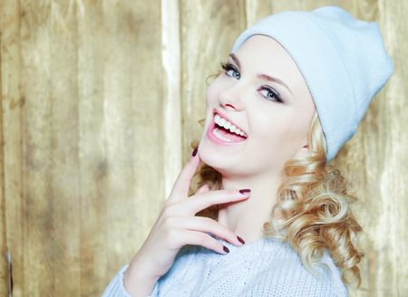 ringlets: Gorgeous smiling young woman with blond ringlets and blue eyes laughing at the camera over a wooden background with copy space Stock Photo