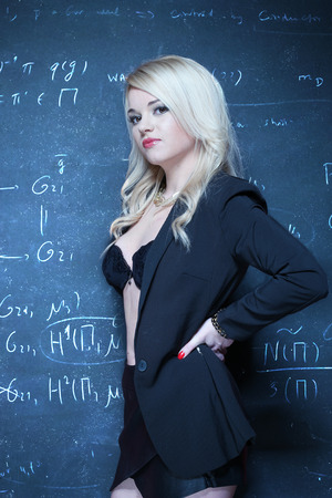 unbuttoned: sexy blonde teacher wearing lingerie on the front of the blackboard chalk Stock Photo