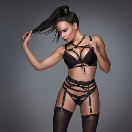garter: Three Quarter Length of Woman with Long Dark Hair in Ponytail Wearing Strappy Bondage Lingerie and Stockings Standing in Studio with Gray Background with Copy Space, Tugging on End of Hair Stock Photo