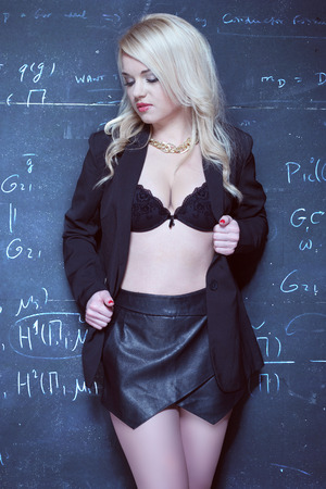 sexy blonde teacher wearing lingerie on the front of the blackboard chalk Stock Photo