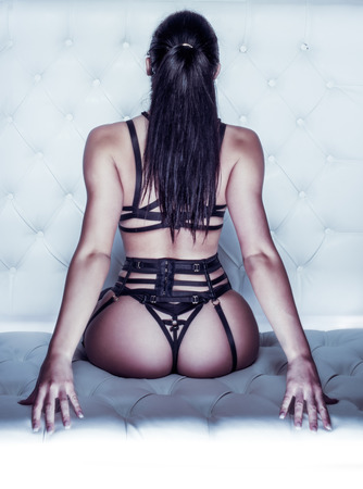 Rear View of Unrecognizable Woman with Long Dark Hair in Ponytail Wearing Strappy Bondage Lingerie and Sitting on Cushion While Leaning Back with Arched Back - Sexy Boudoir Portrait