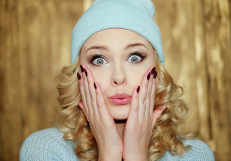 shushing: Surprised or shocked attractive young blond woman with ringlets and huge blue eyes holding her hands with manicured red nails over her mouth in a close up head shot