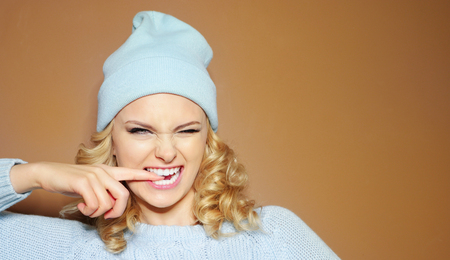 shushing: Gorgeous young woman with blond ringlets in a green knitted winter outfit and hat biting her finger