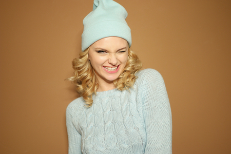 ringlets: Gorgeous young woman with blond ringlets in a green knitted winter outfit blinking her eye