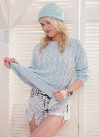 tugging: sexy blonde woman wearing shorts sweater and hat on white