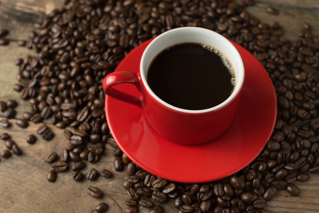 black and red: red cup of black caffee with the beans surrounding on wood