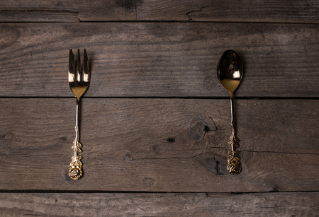 criss: golden and silver vintage forks and spoons on old wooden table
