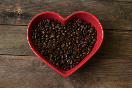 shaped: Coffee beans background and in the red heart shaped bowl