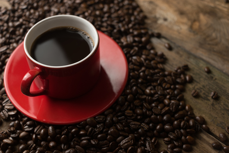 caffee: red cup of black caffee with the beans surrounding on wood